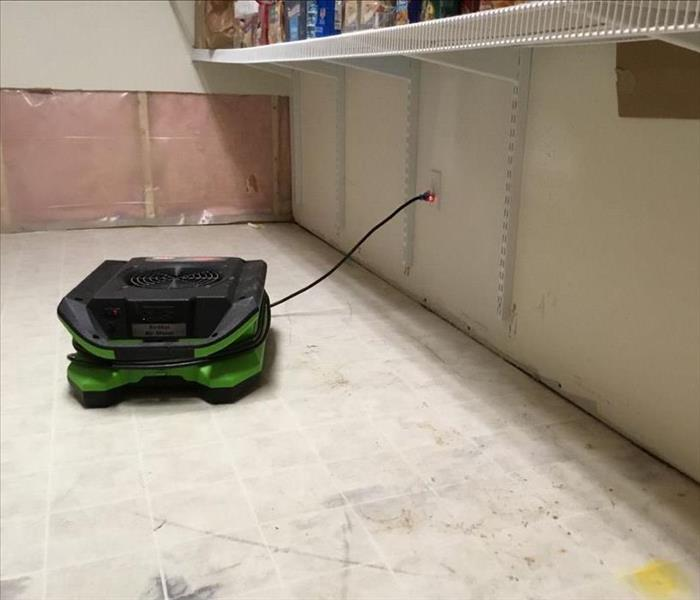 Drying equipment on floor underneath food shelving with back wall partly cut out