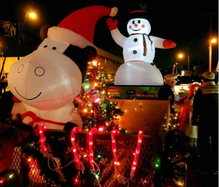 Lighted blow-up snowman and cow with Santa hat and holiday lights on a trailer