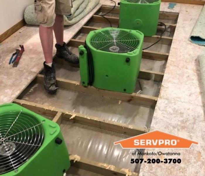 Three green fans on top of subflooring.