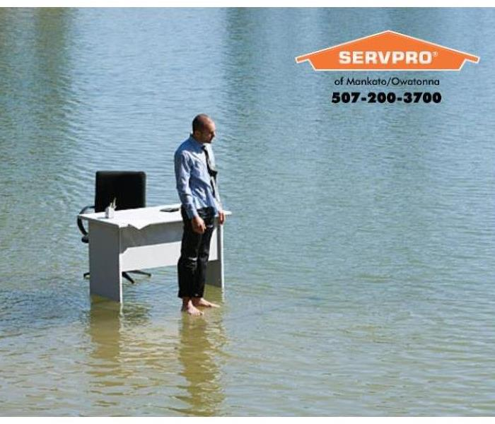 Man standing in front of desk surrounded by water