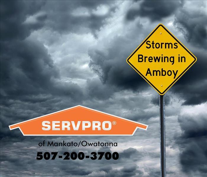 "SERVPRO logo and yellow road sign stating ""Storms Brewing in Amboy"" in front of a dark and cloudy sky."
